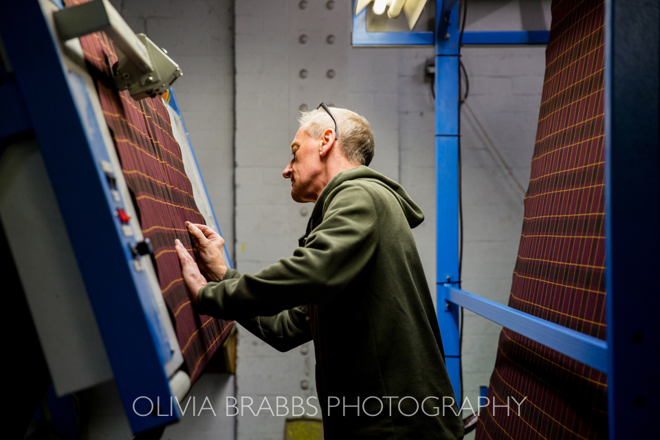hand checking fabric at marton mills in Yorkshire www.oliviabrabbs.co.uk