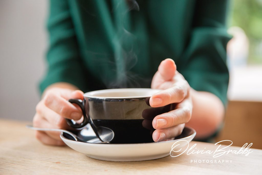 steaming cup of coffee with hands