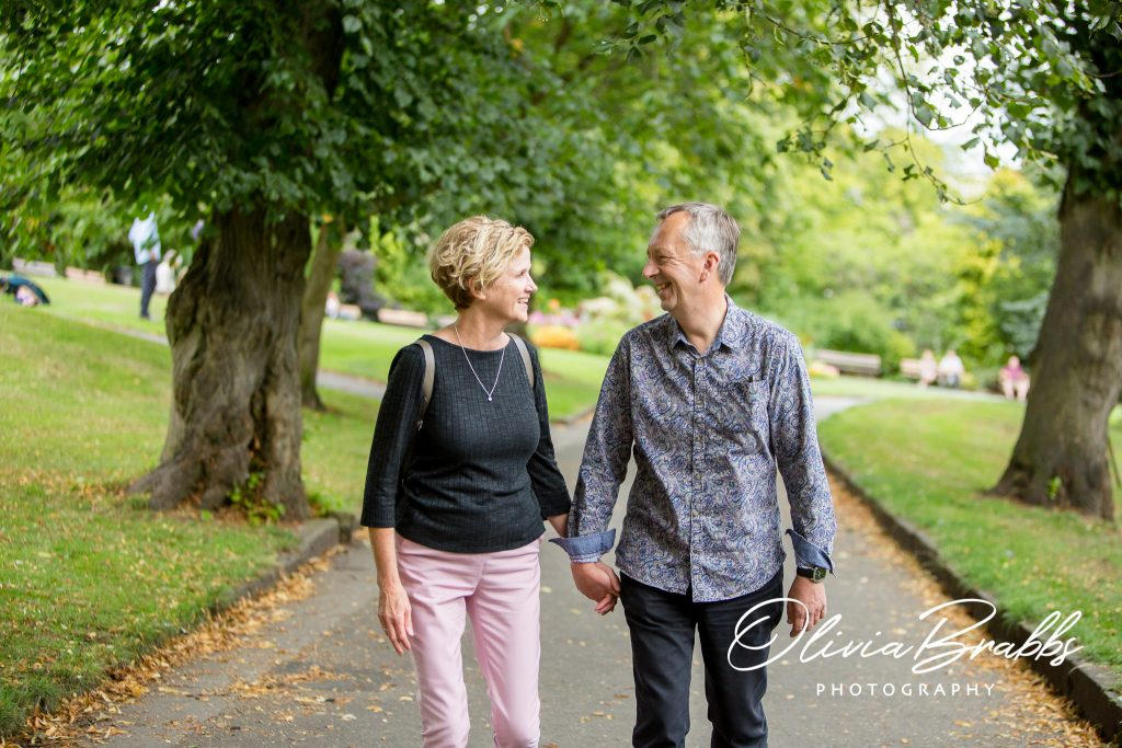 portrait of couple walking in park photographed for the hearing suite