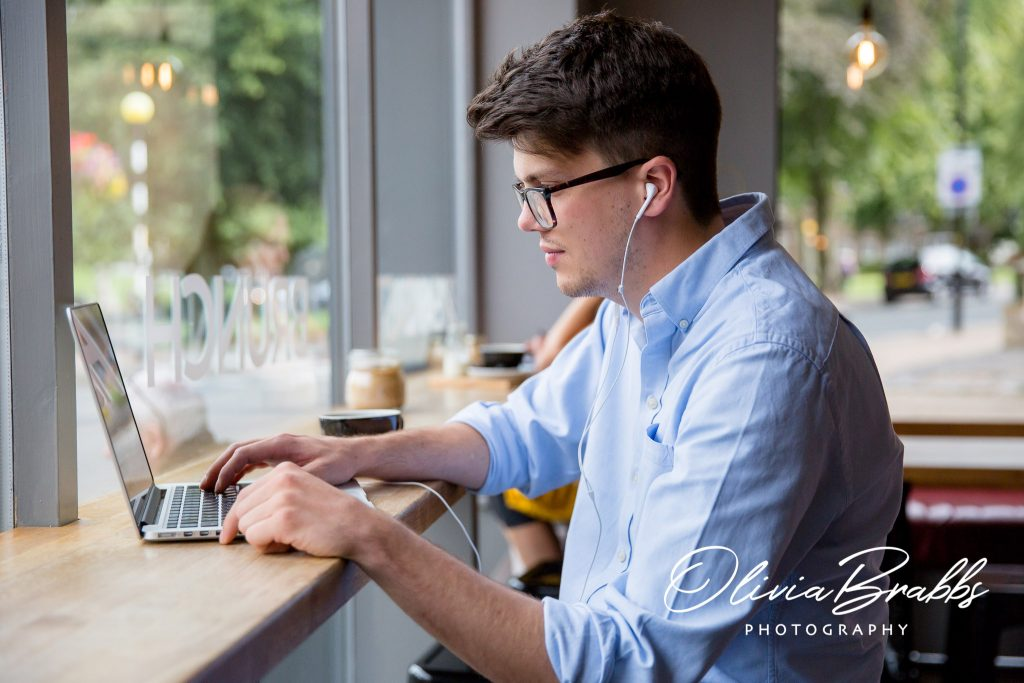young man in coffee shop at lap top for the hearing suite in harrogate