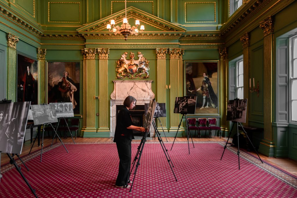 female photographer olivia brabbs setting up print panels in york mansion house for fashion photography exhibition