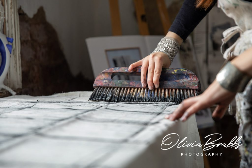 close up image of artist ros johnson at work showing hand and fabric brush