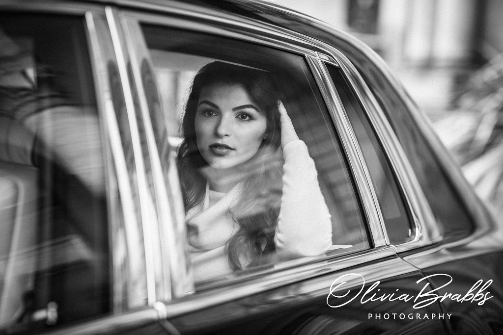 close up fashion portrait of female model in window of rolls royce phantom