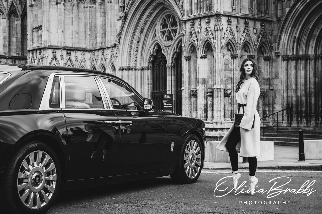 fashion photography at york minster featuring female model and ballerina in Jaeger coat en pointe walking to rolls royce phantom