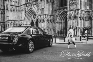 fashion photography at york minster featuring female model and ballerina in Jaeger clothes en pointe walking to rolls royce phantom