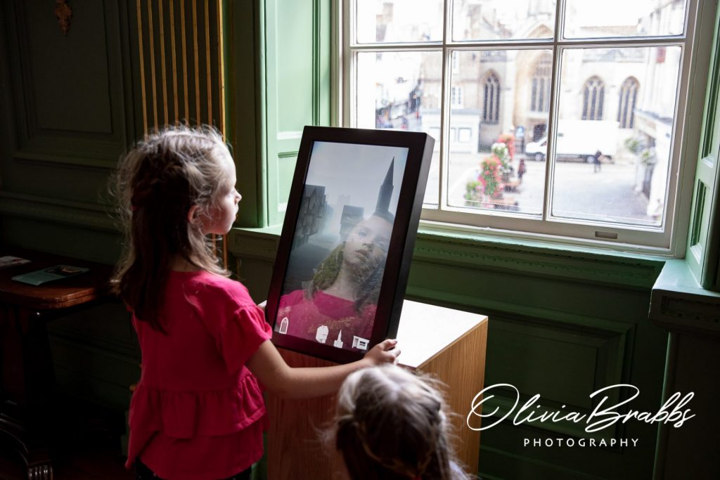 girl looking at interactive screen display at york mansion house showing history of st helens square