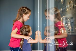 two girls discovering silver objects on display at york mansion house with reflections in glass