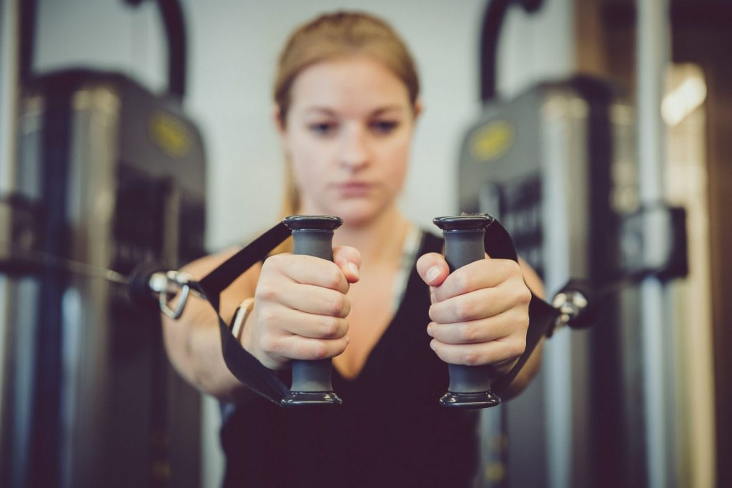 portrait of young woman resistance training at supersonic fitness in york